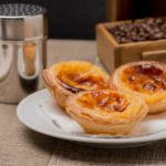 Pasteis de Nata or Portuguese Custard Tarts on wooden table.